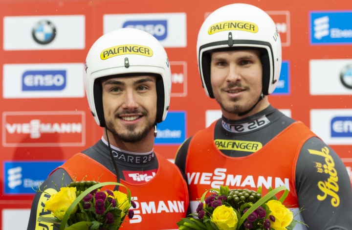 Austria's Thomas Steu, right, and Lorenz Koller, left, pose during the winning ceremony for the men's doubles luge race of the Luge World Cup in Altenberg, Germany, Saturday, Jan. 11, 2020. (Matthias Rietschel/dpa via AP)