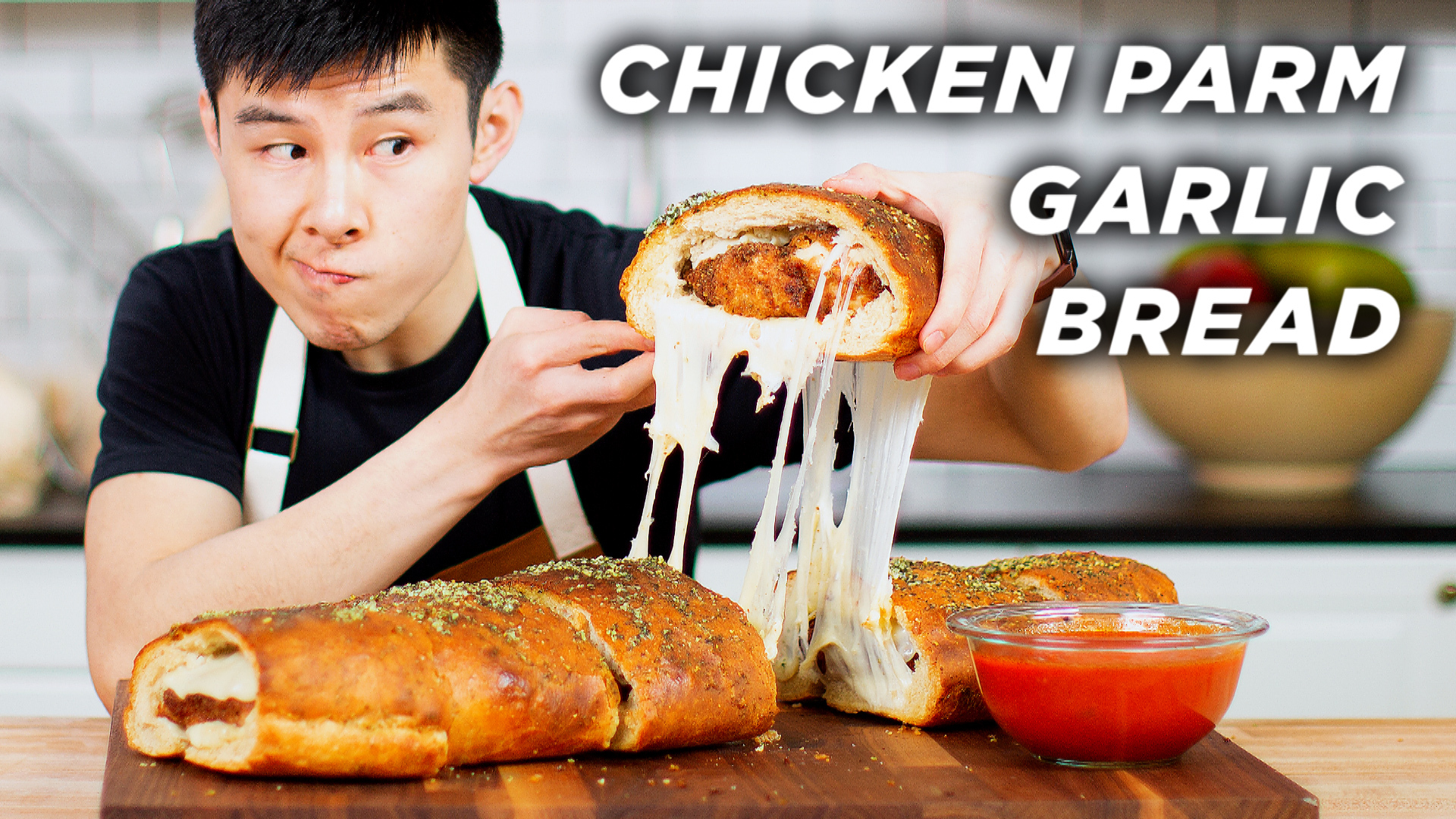 Alvin holds up a giant piece of cheesy chicken parm garlic bread.