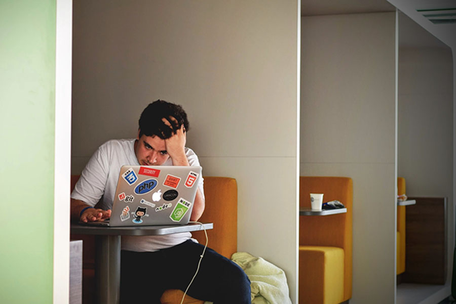 Student with head in hand on a laptop