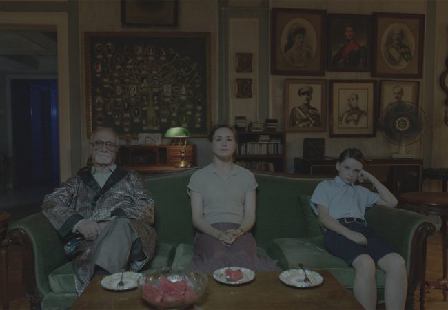 The family (Thanasis Papageorgiou, Valery Tscheplanow, Victor Khomut) watches TV in SON OF SOFIA. Photo credit: Dionysis Eftimiopoulos.