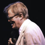 Garrison Keillor on stage with microphone Winona Minnesota performance