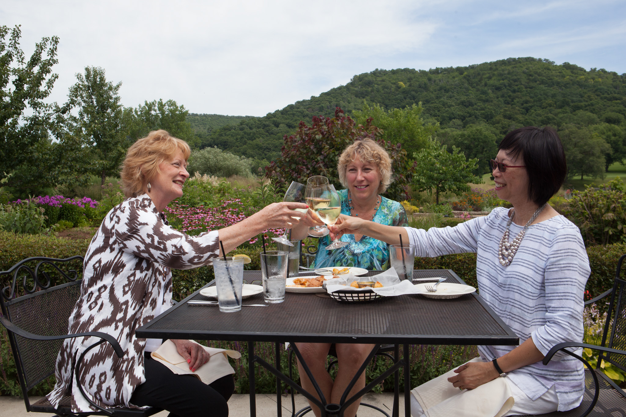 women toasting with glass of wine next to the beautiful view from the Signatures patio