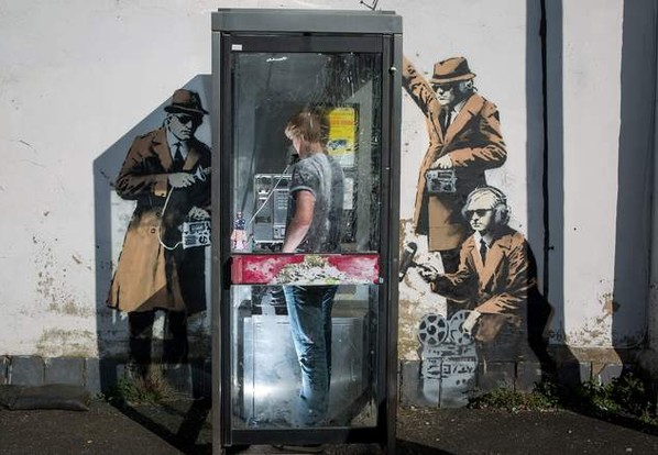 Until the fence was put in place, residents had to deal with a frequent stream of Banksy fans posing for a phone booth pic. (Image via newsonia)