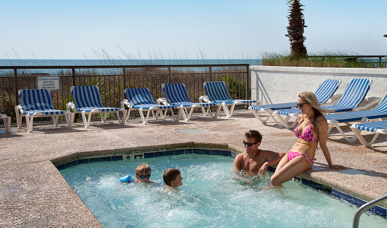 Family relaxing in the oceanfront hot tub at Captain's Quarters Resort in Myrtle Beach, SC
