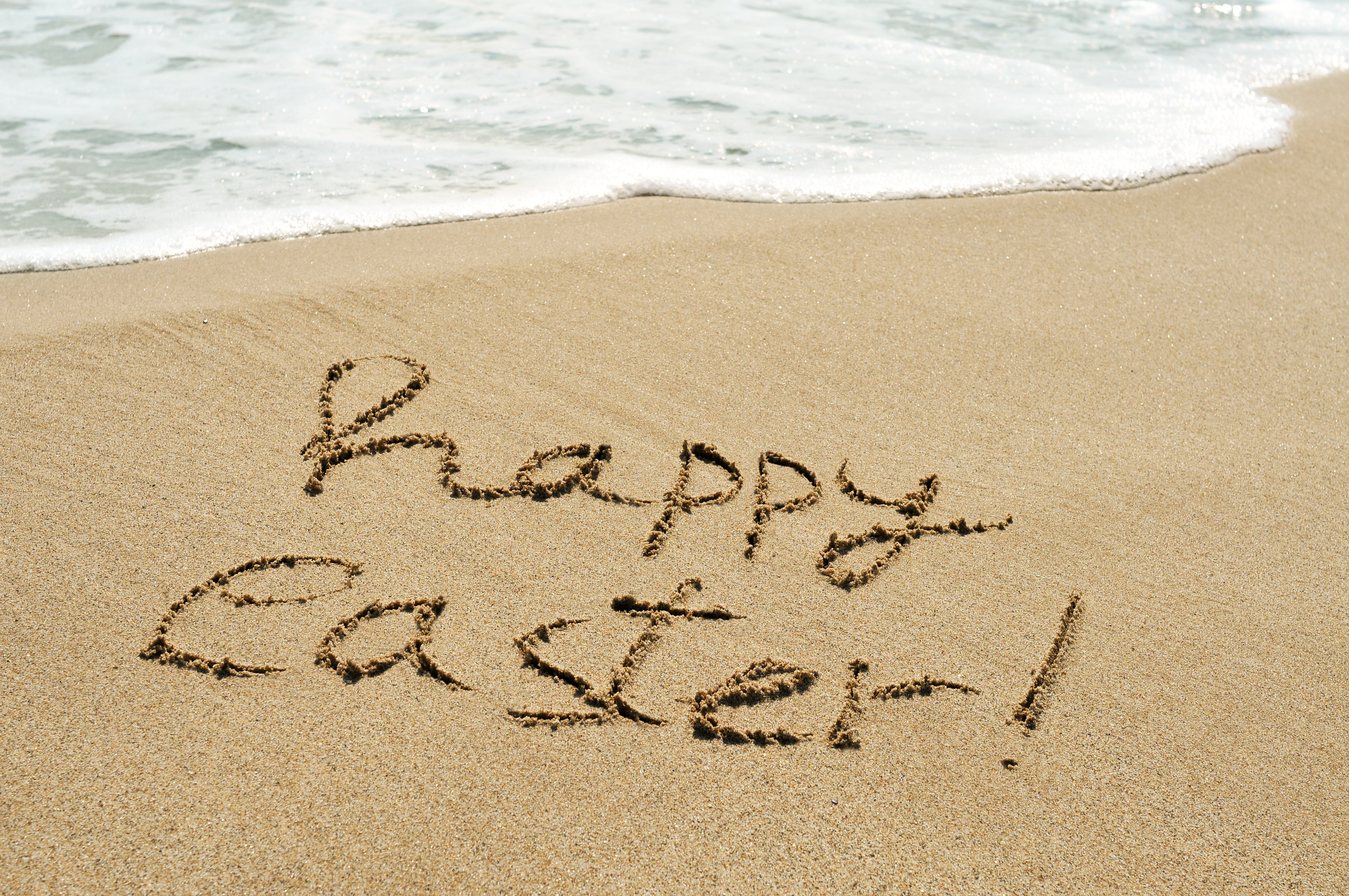 Happy Easter written in the sand