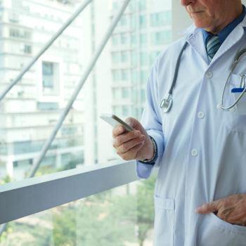 Mature doctor messaging in hospital corridor