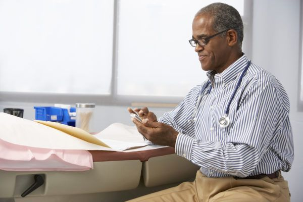 Male Doctor In Surgery Using Mobile Phone
