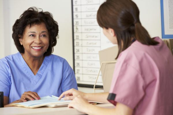 Two Nurses In Discussion Sitting At Desk