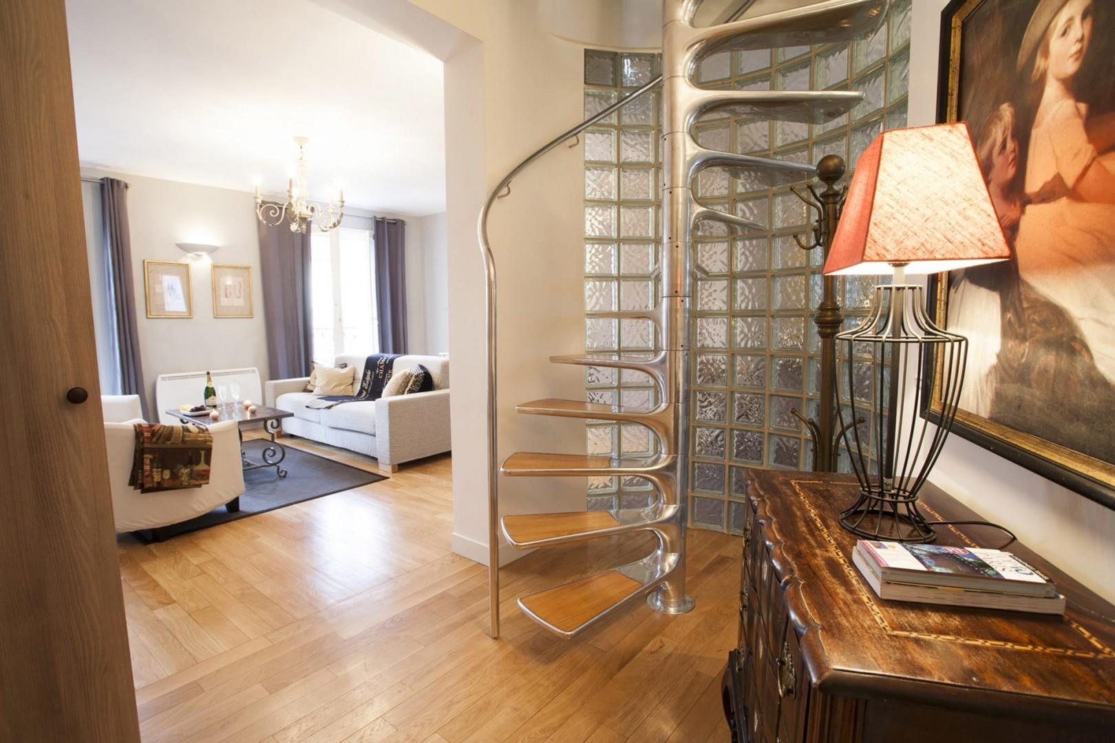 The spiral staircase adds even more flair to the beautiful apartment!
