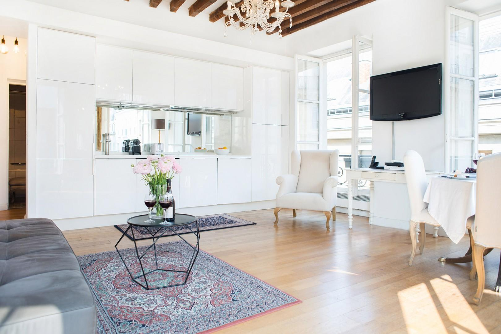 White decor, high ceilings, and bright windows create a spacious atmosphere.
