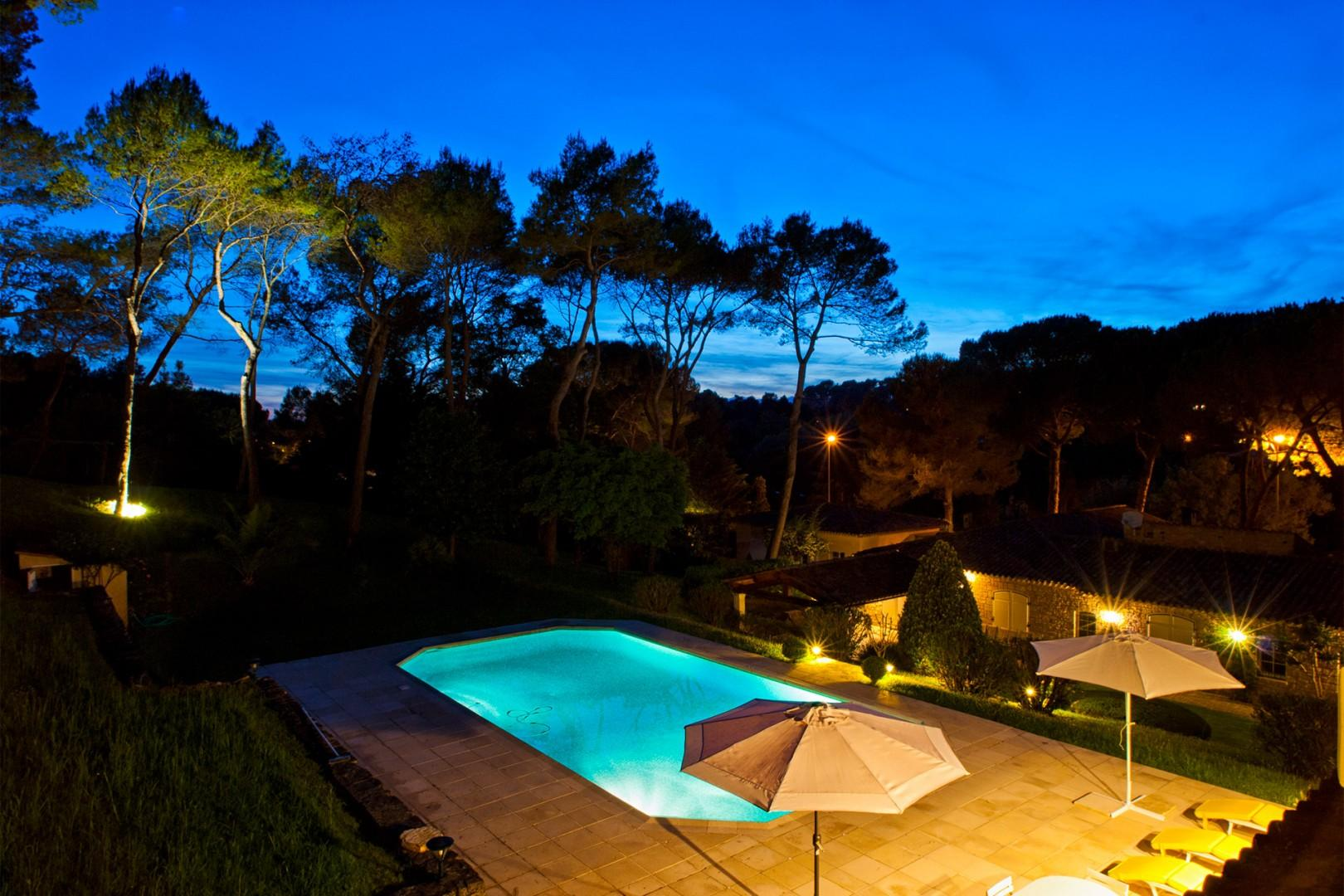 View of the pool at night from the house