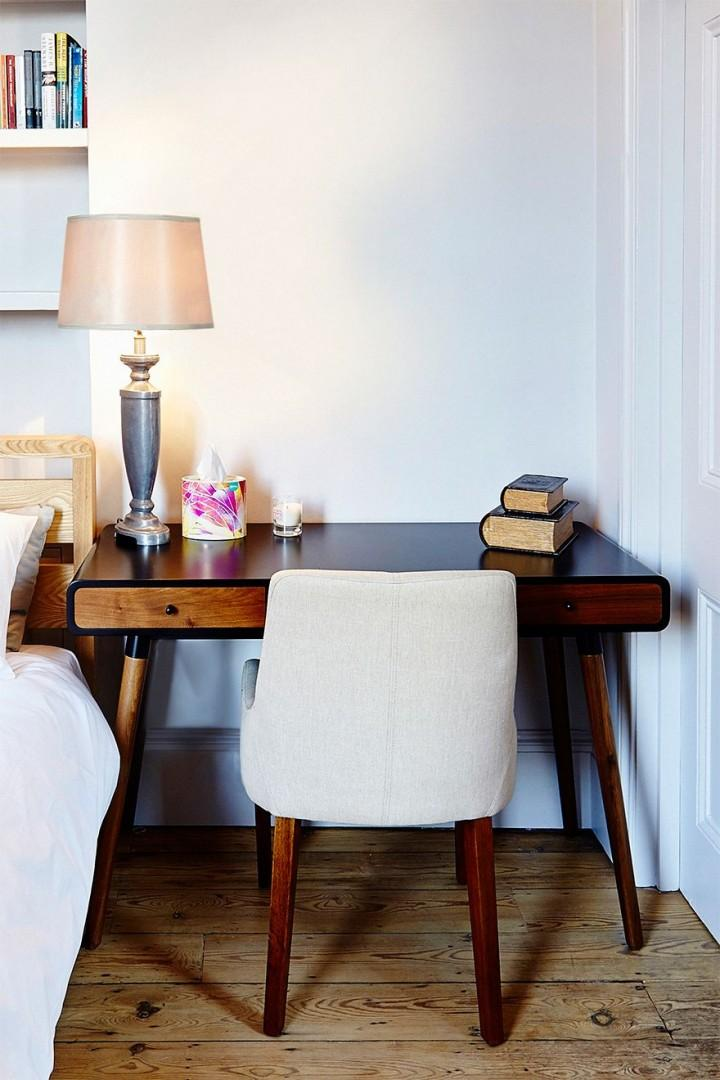 A Charming little desk next to the bed