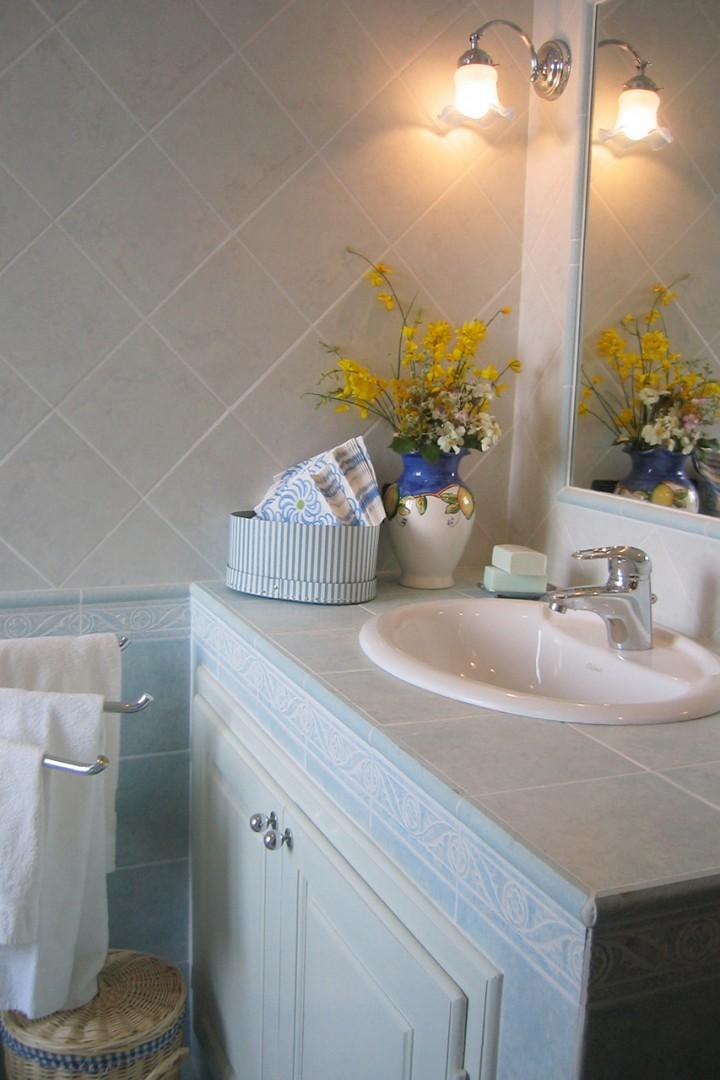 Bathroom 1 has a jetted bathtub with a handheld showerhead. Plenty of countertop space.