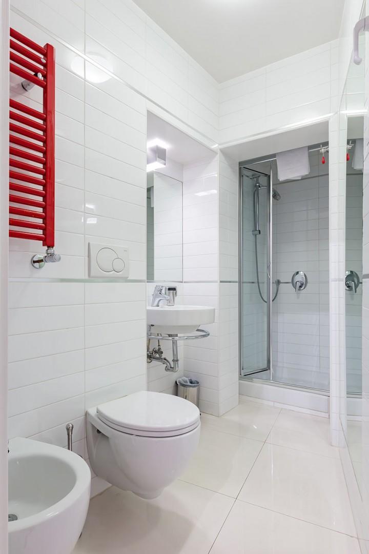 En suite bathroom 2 has bright white tiles and large shower.