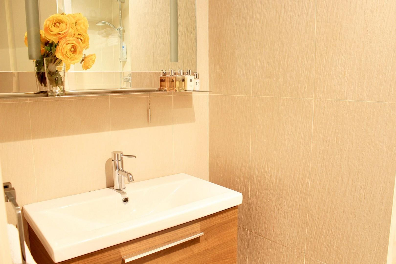 Spacious sink with storage below and overhead mirror