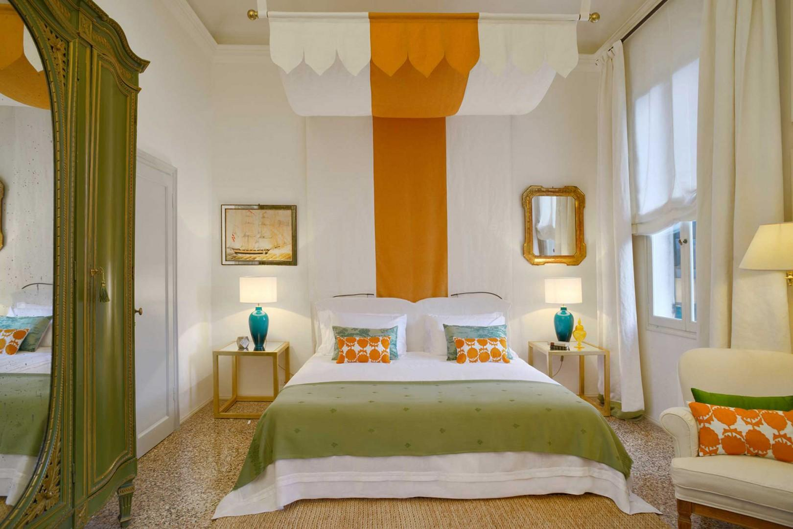 A canopy with a dramatic orange strip decorates the bed in bedroom 1.