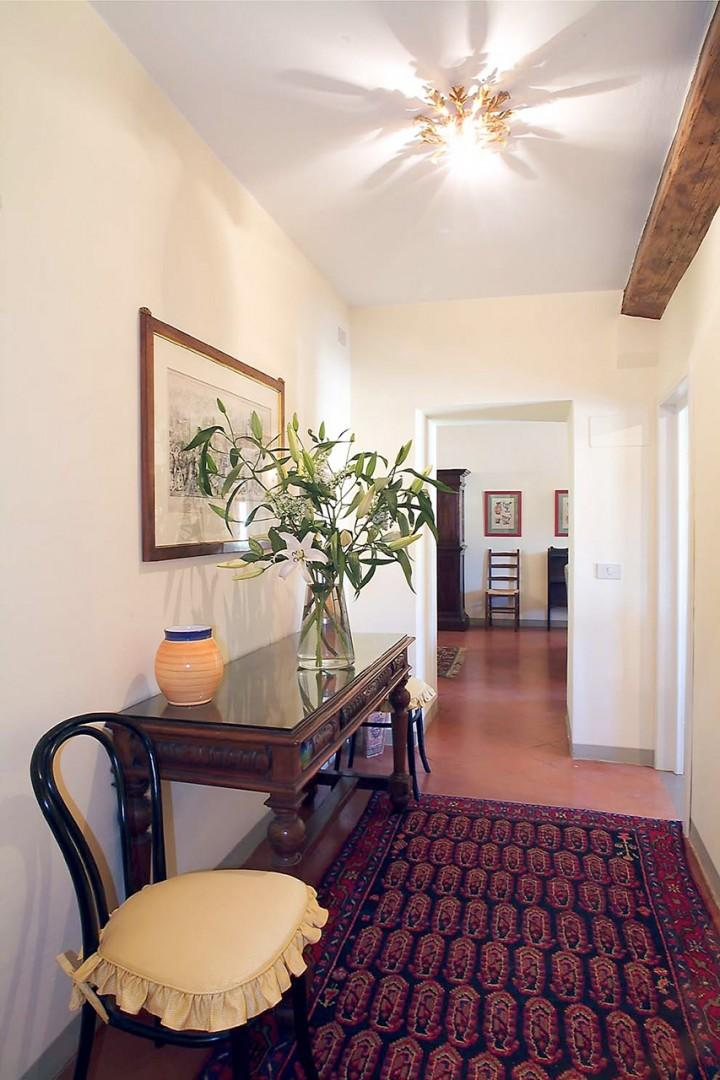 The entry hallway with Italian floor tiles leads from the apartment's front door to the living room.