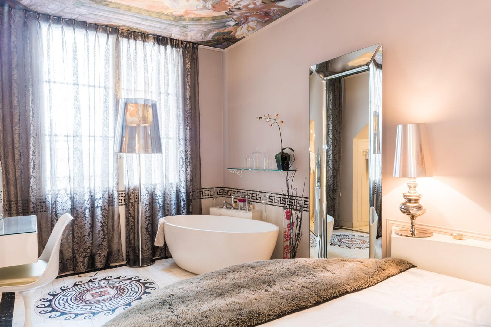 The bedroom is an oasis with a large soaking bathtub.