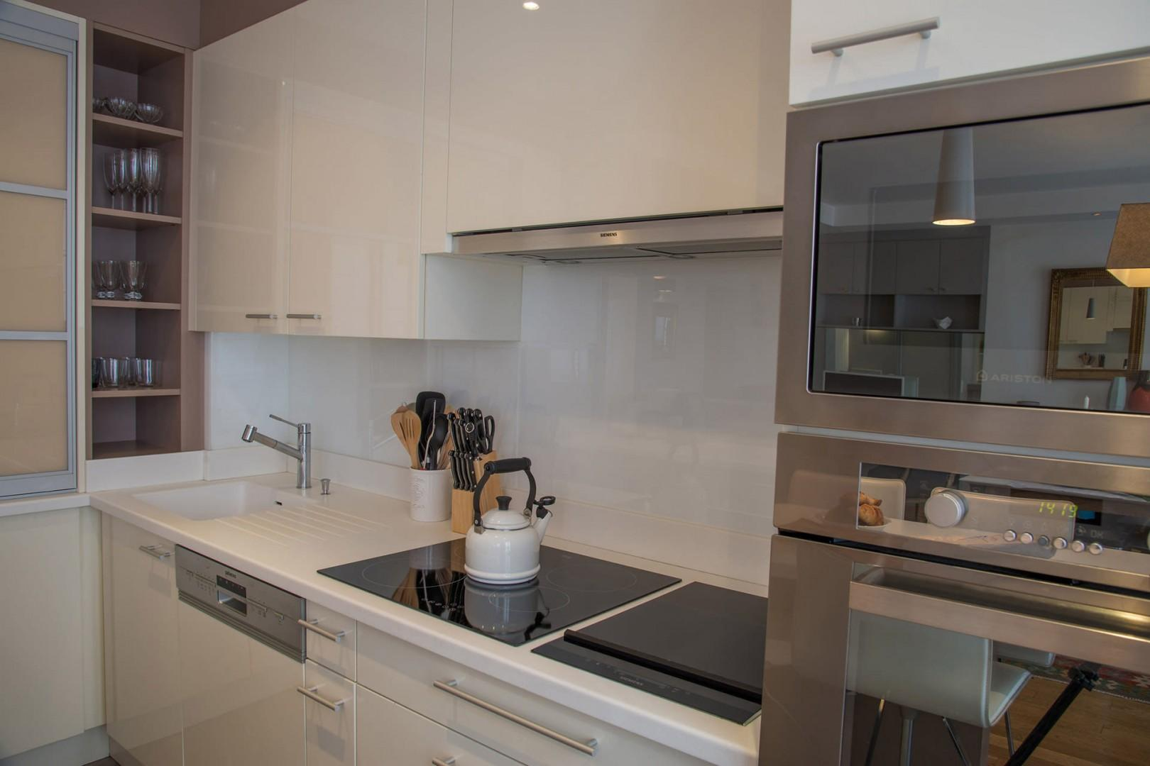 The kitchen features an induction cooktop stove and modern appliances.