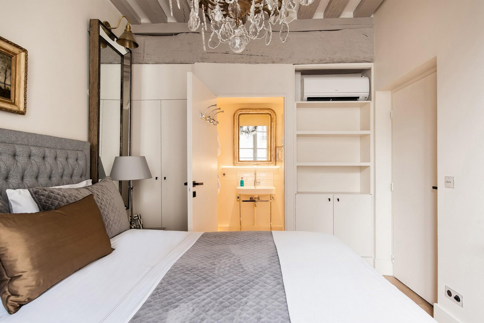 The bedroom has an en suite bathroom and ample storage.