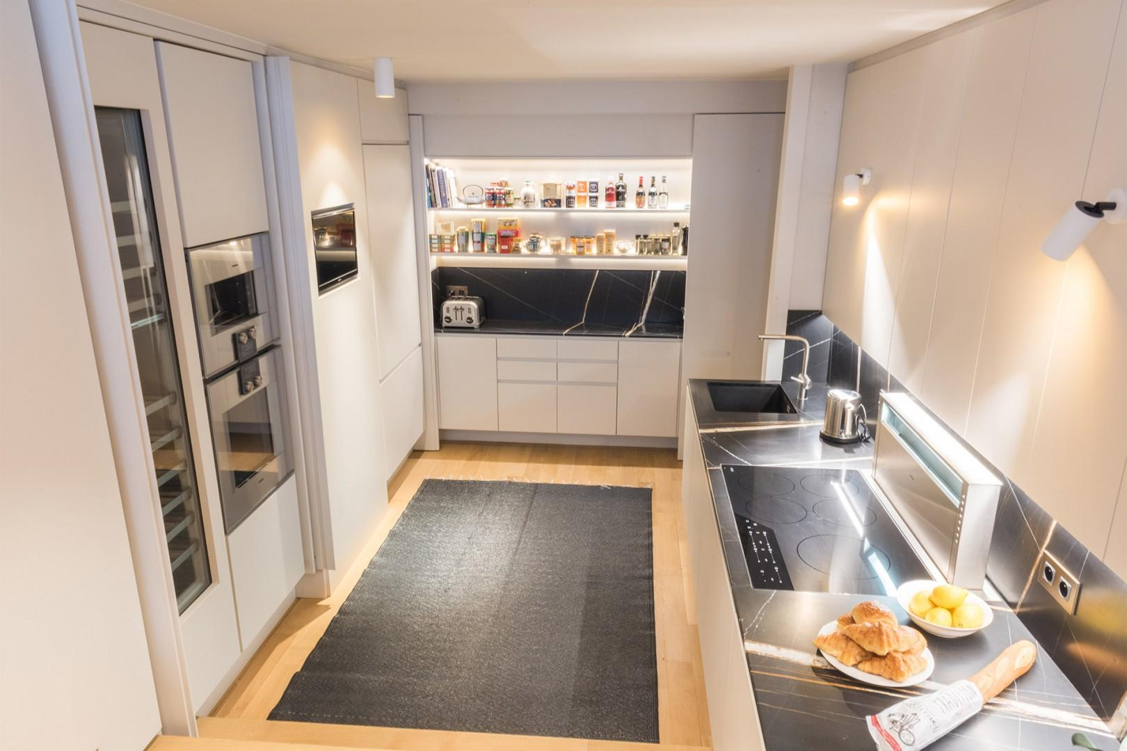 View into the modern kitchen, down a few steps from the living room