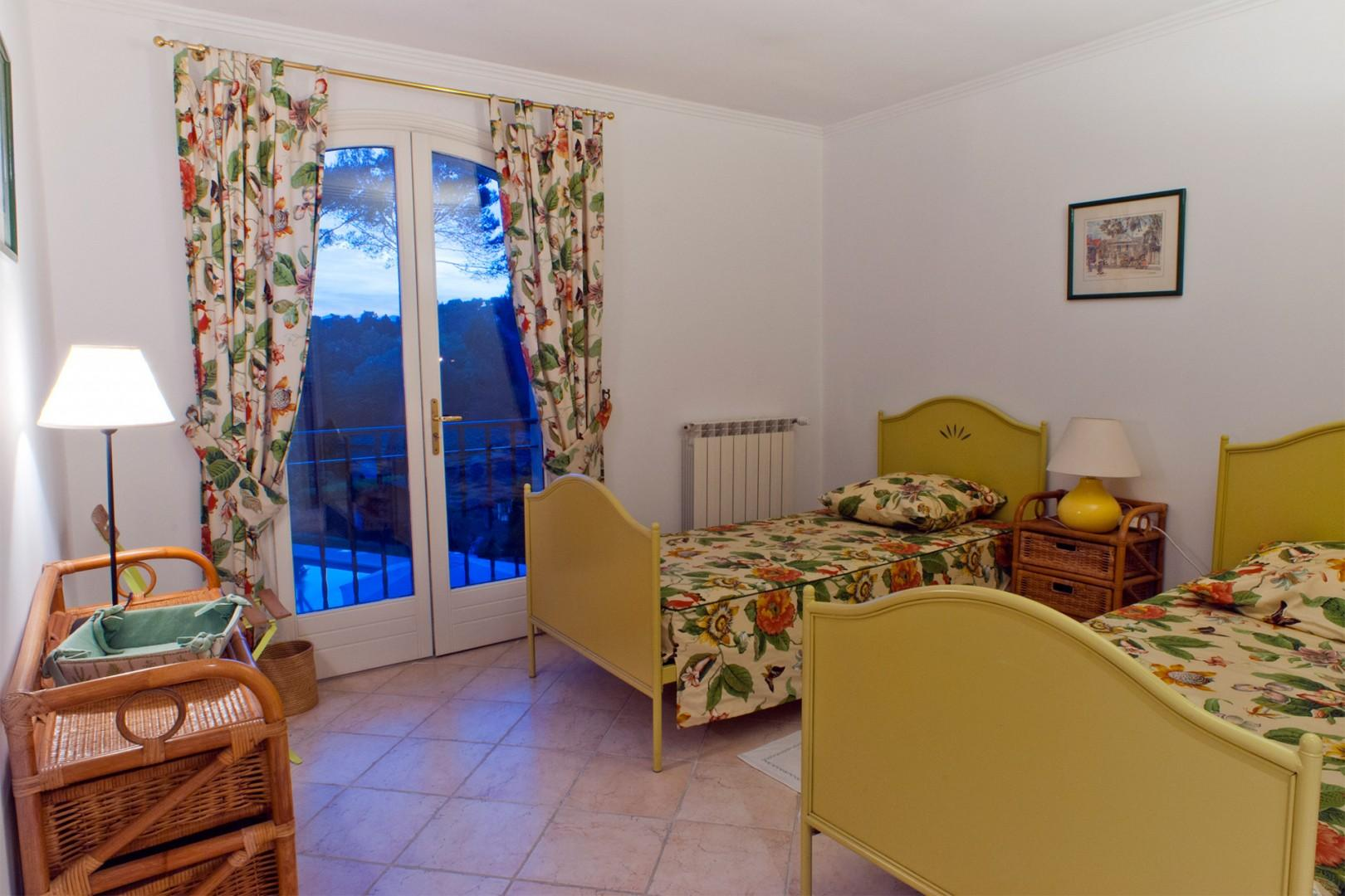 Bedroom two with two single beds, en suite bathroom and pool views