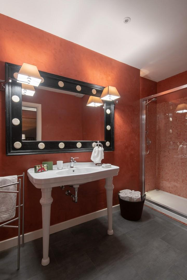 Spacious en suite bathroom with sink, shower and heated towel racks.