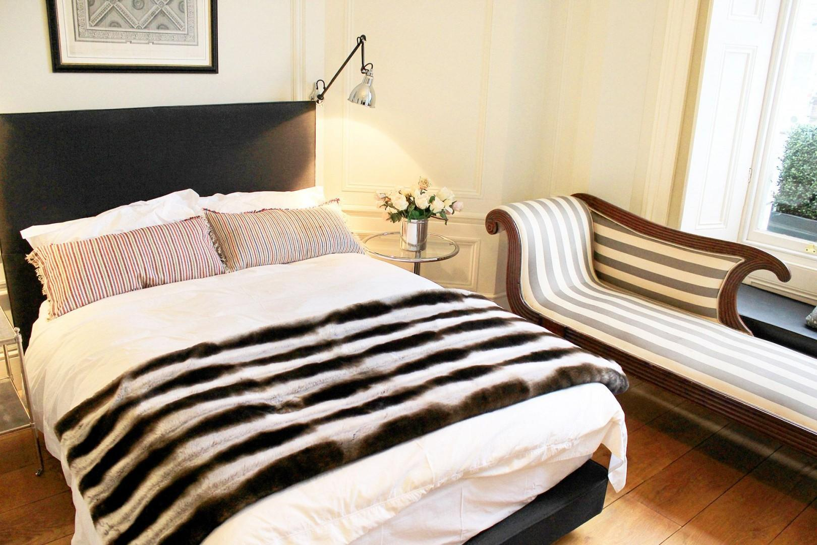 Beautiful bedroom with comfortable bed and chaise longue