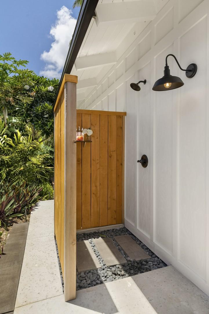 Tranquil outdoor shower, surrounded by lush greens.