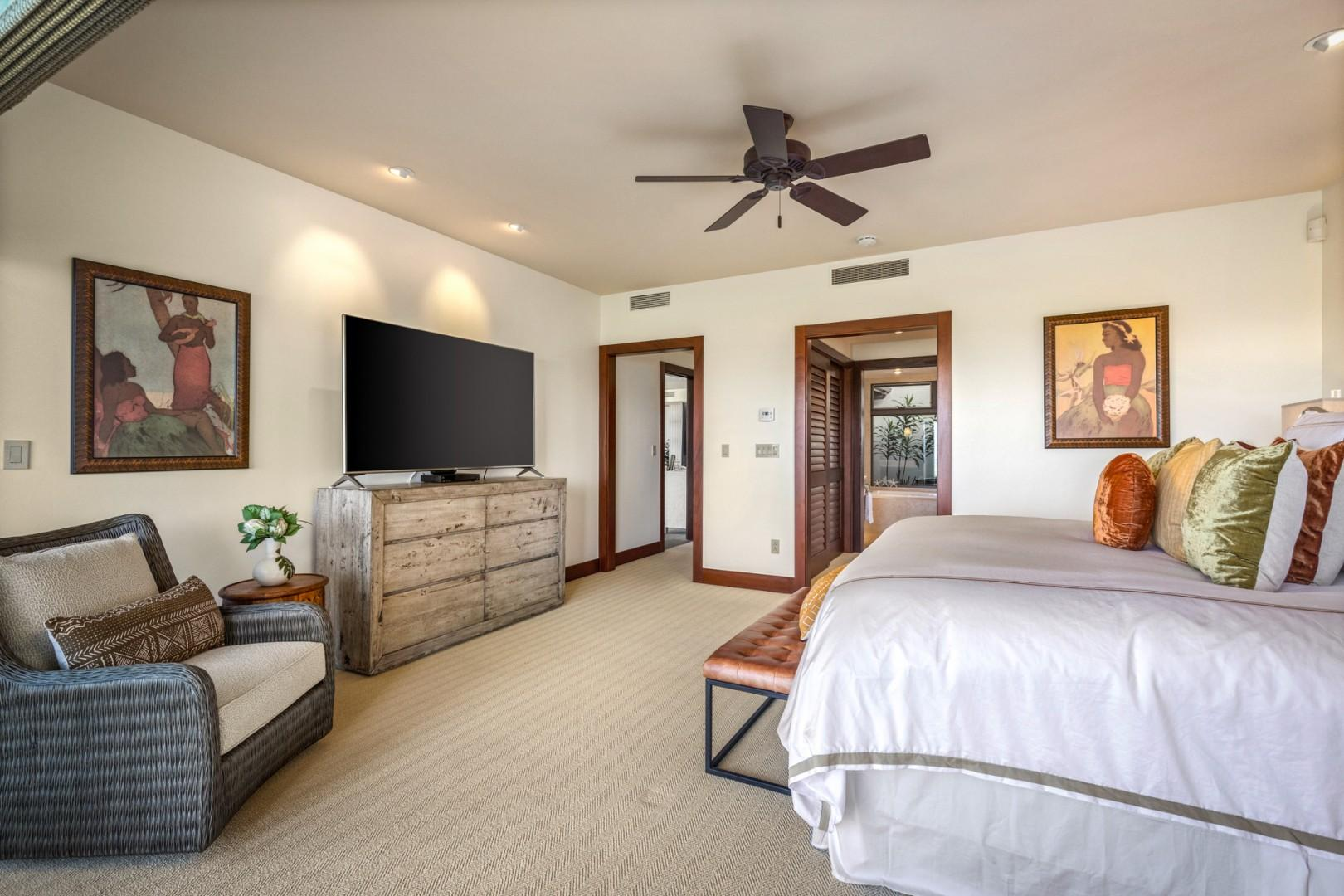 View of ocean view master suite toward walk-in closet and en suite bath showcasing large flat screen TV.
