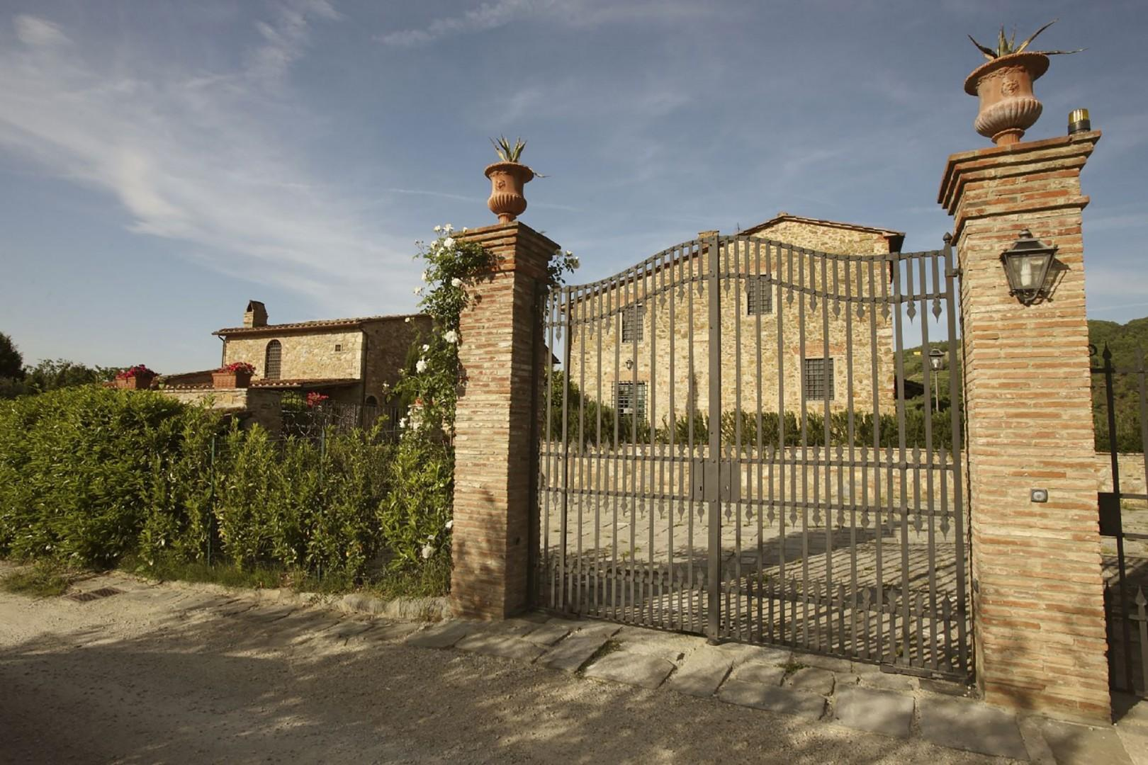 The front gate leads to a generous, paved parking area outside the villa.