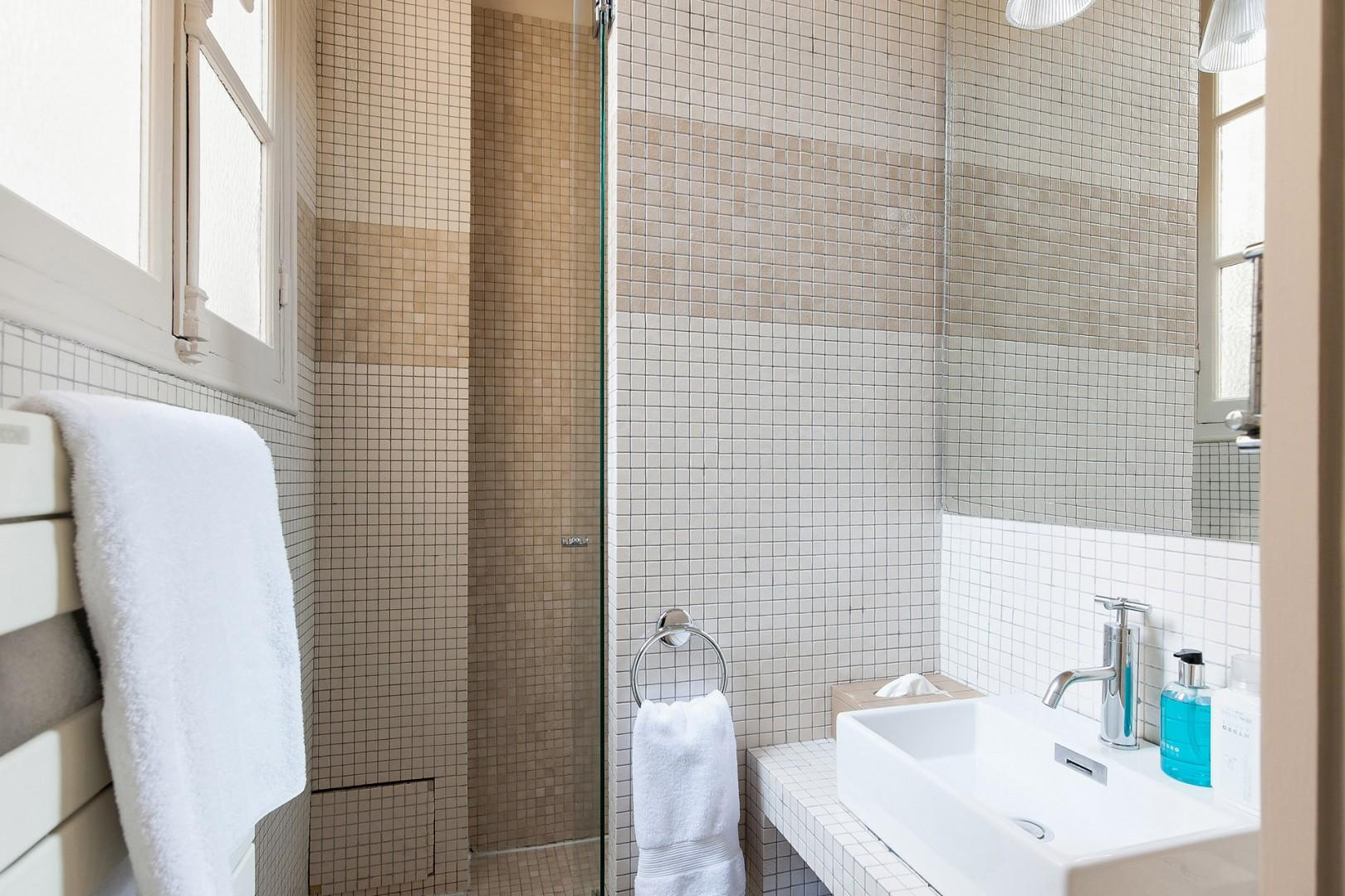Bathroom 2 is equipped with a shower, sink and heated towel racks.