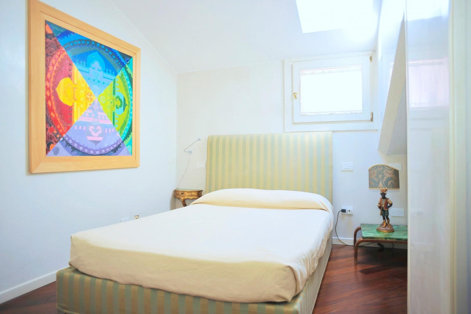 There is an alcove on the side of the bed with a low ceiling.