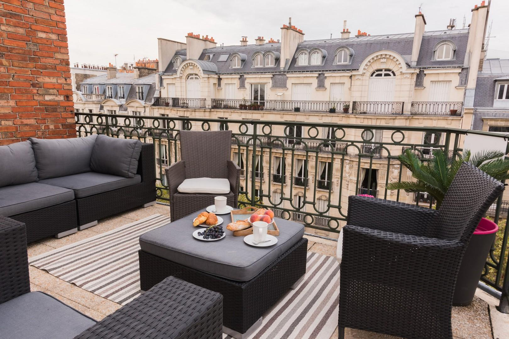 Lounge on the comfortable sofa and chairs as the sun sets over the rooftops of Paris.