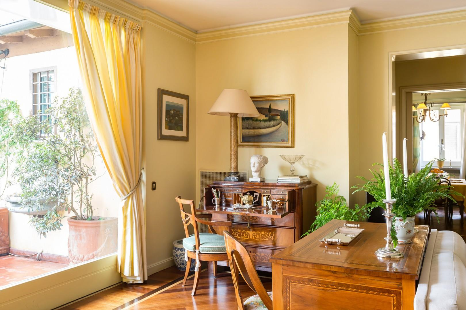 An antique desk in the corner of the living room. You can see the dining room across the hall.