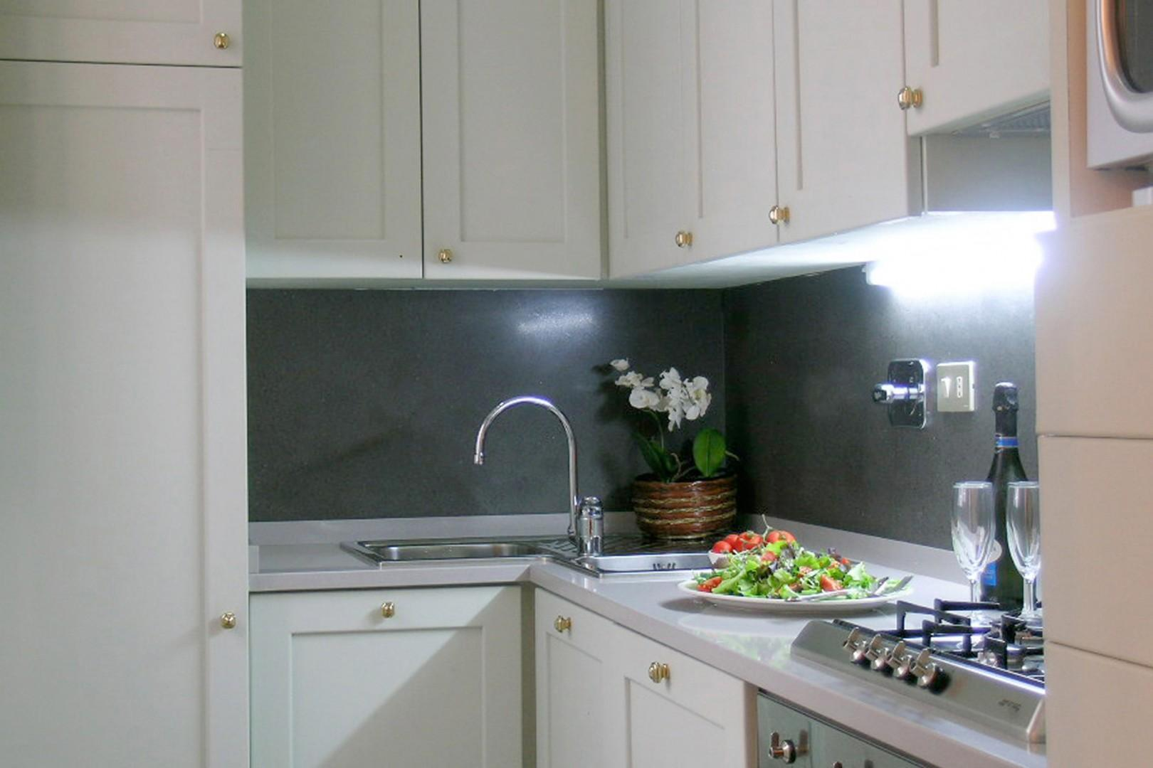 A modern kitchen glistens with microwave, oven, four burner stovetop and dishwasher.