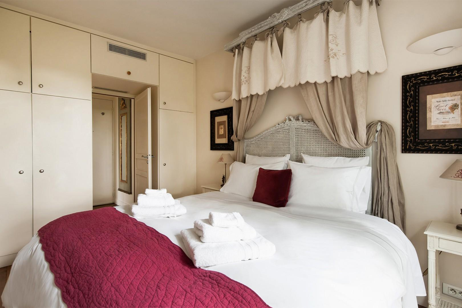 The airy bedroom is furnished with beautiful pieces.