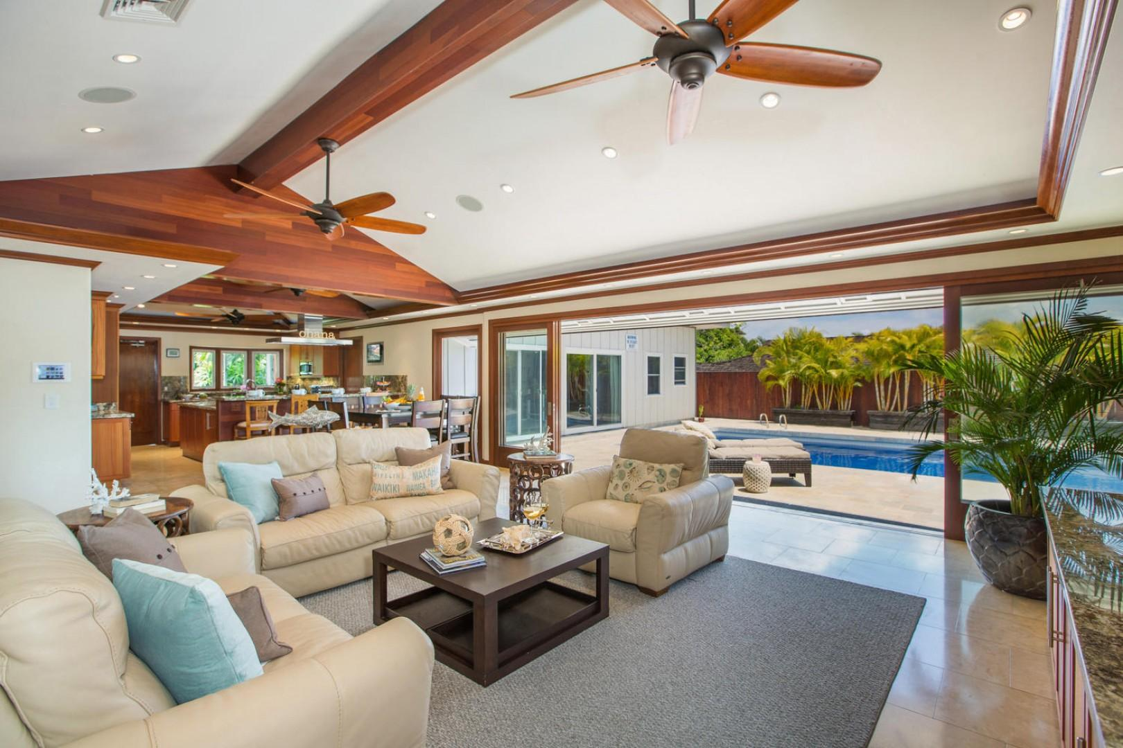 Main living room and kitchen with natural travertine stone, cherry wood throughout, and luxurious lighting details.