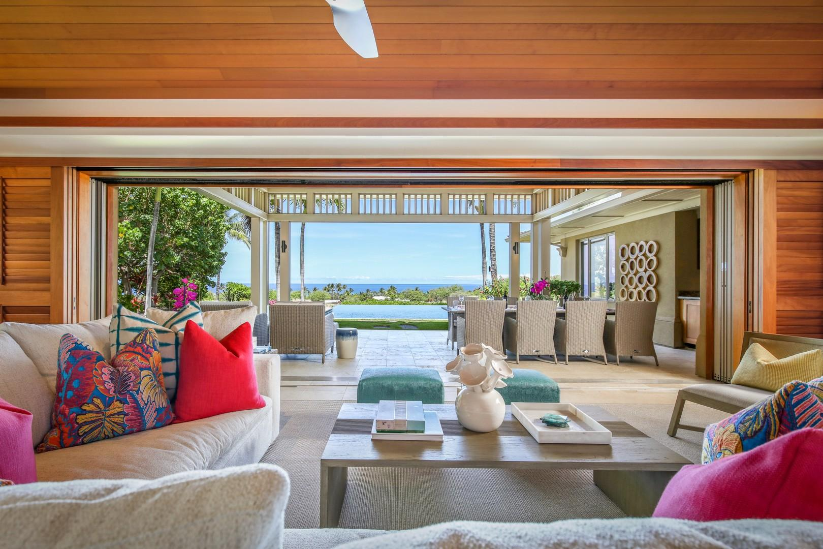 Great room seating expanding to the covered lanai, pool, and ocean beyond.