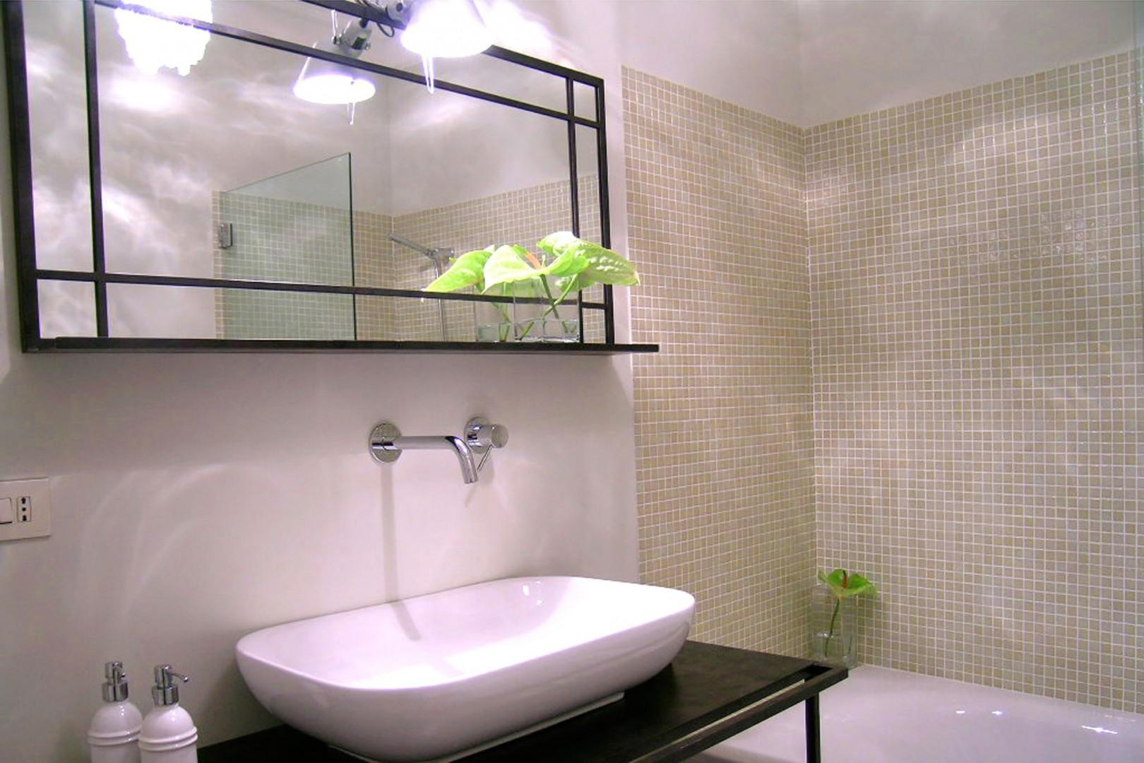 Pale sage colored tiles line the large bathtub walls of the en suite bathroom of bedroom 1.