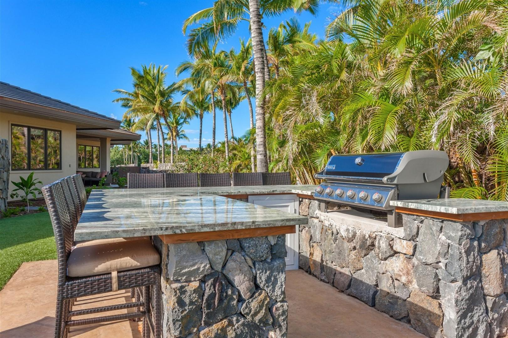 Outdoor built-in 6-burner Coyote BBQ Grill with ample counter area and bar seating.