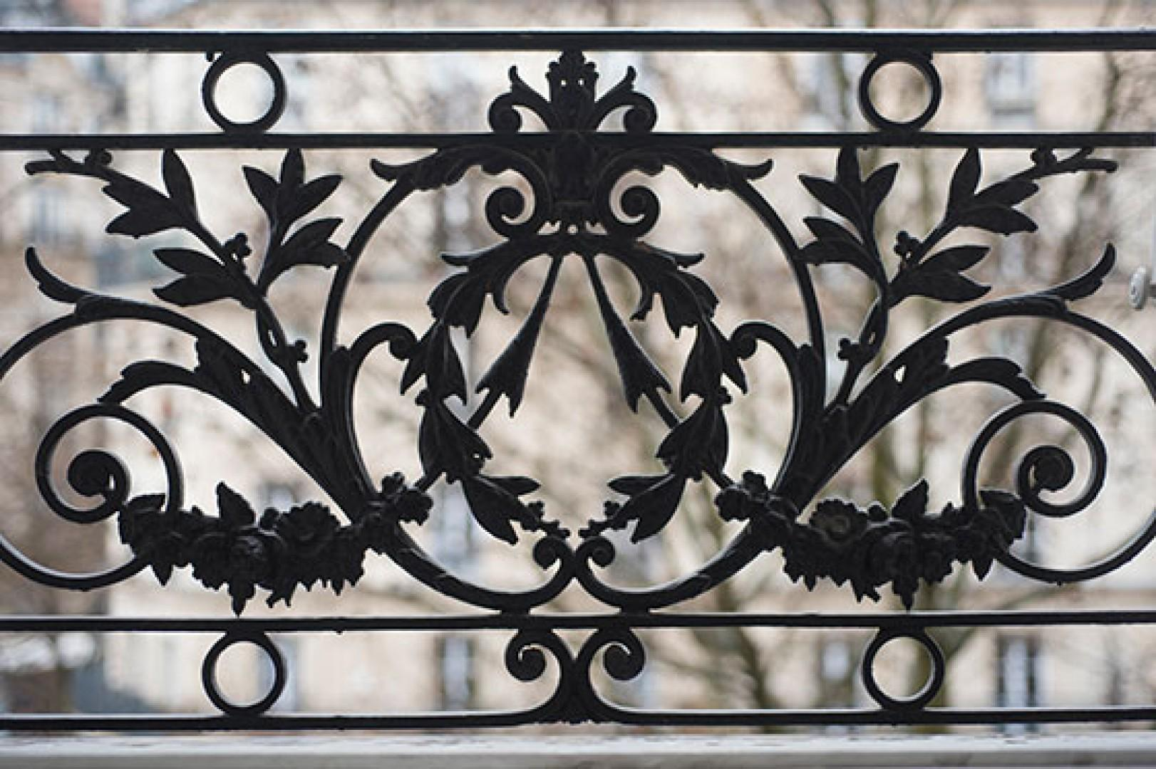 The apartment is filled with chic Parisian touches, like this iron grillwork on the window.