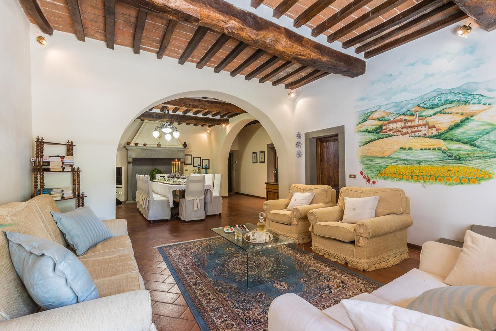 Comfortably furnished living room with beamed ceilings and terra cotta tile floors.