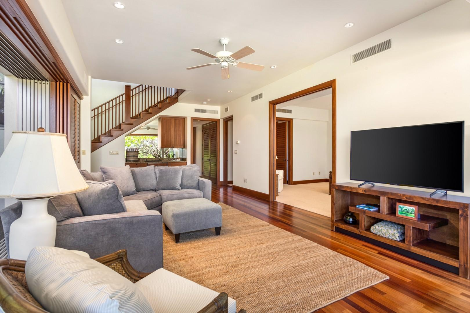 """Downstairs """"bonus living room"""" off master suite with gorgeous hardwood floors, wet bar and pocket doors to the lower lanai."""