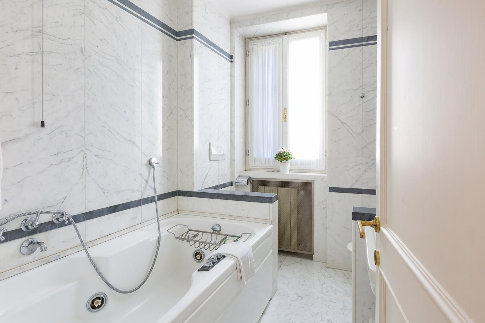 The bathroom features a jacuzzi tub, telephone-style shower, toilet, bidet and sink.
