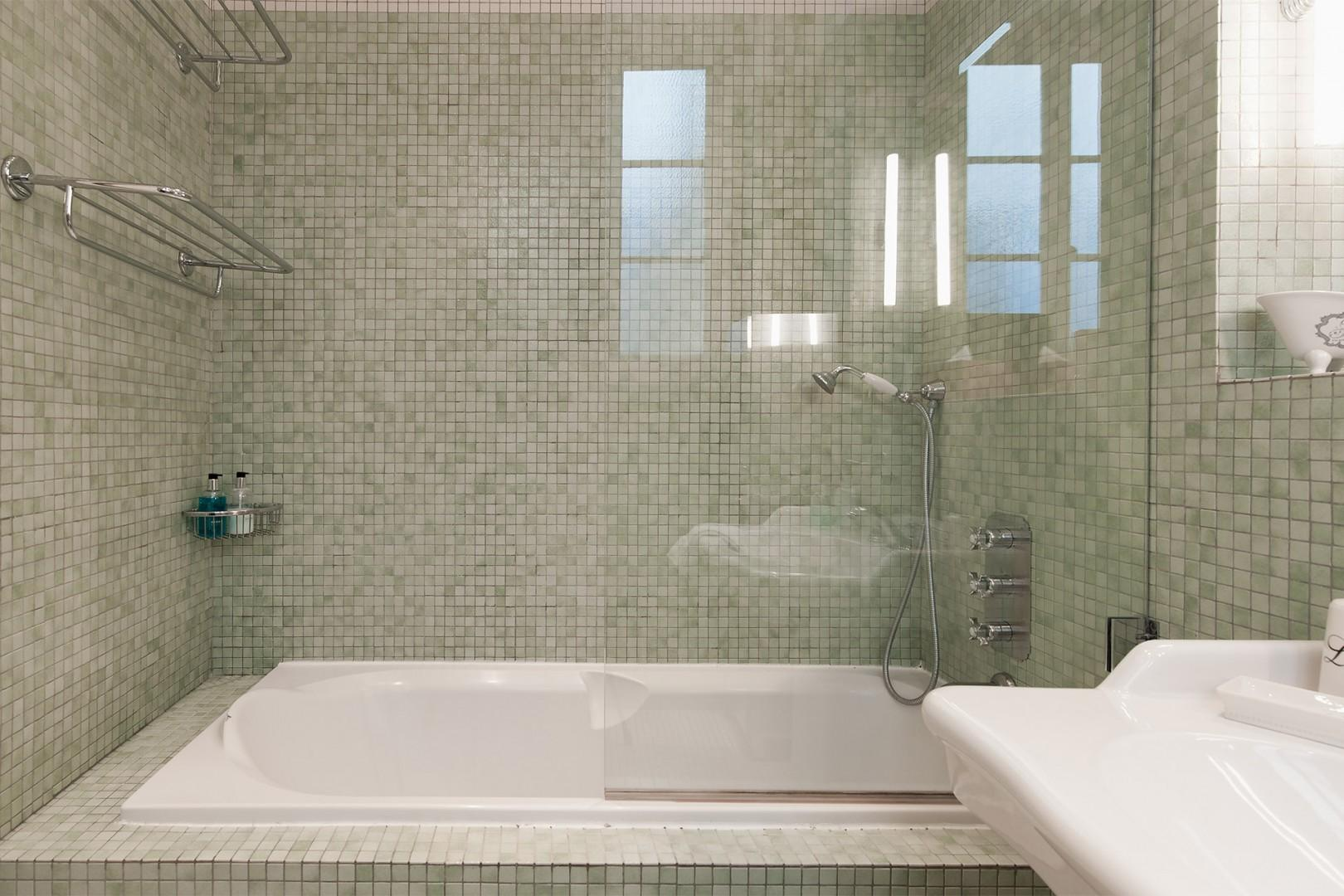 Take a relaxing bath surrounded by glistening tiles.