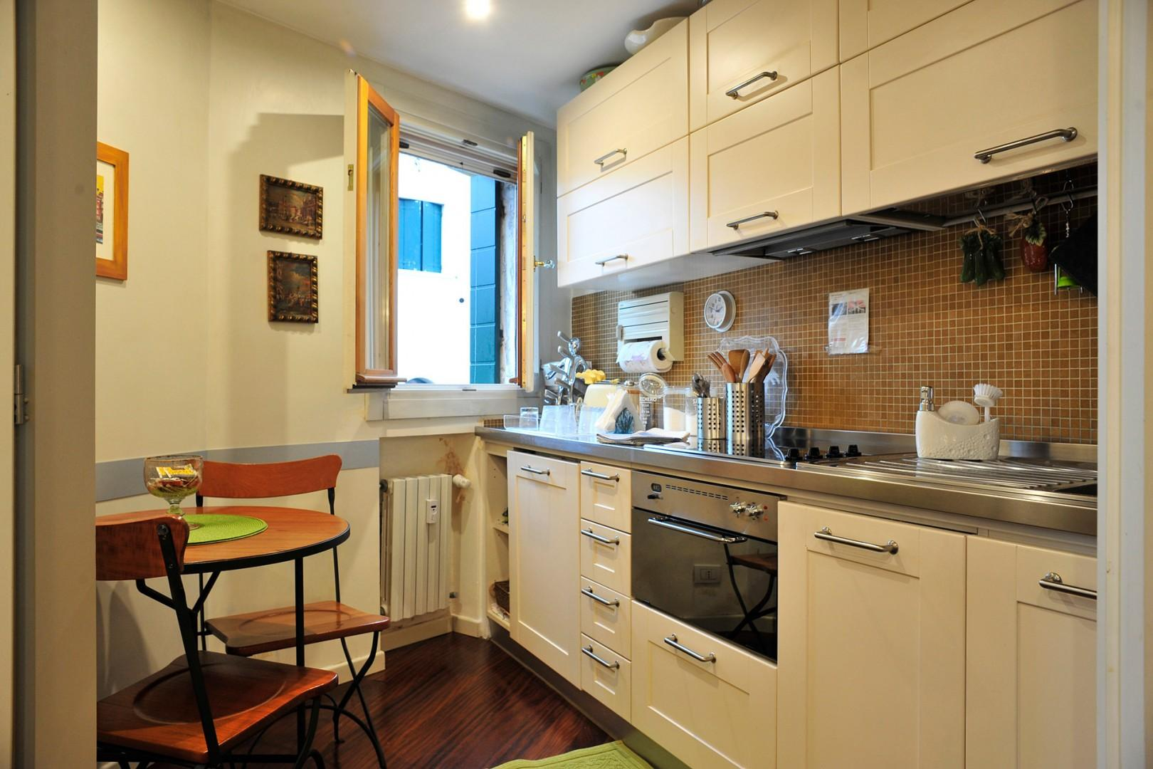 The small complete kitchen of Serenata has a breakfast table and pretty view out the window.