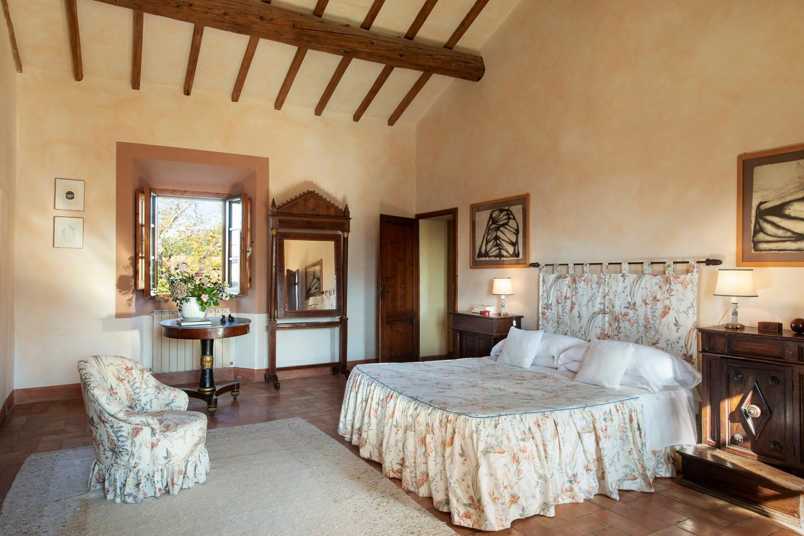 Restful bedroom with windows overlooking the garden and olive orchards to one side.