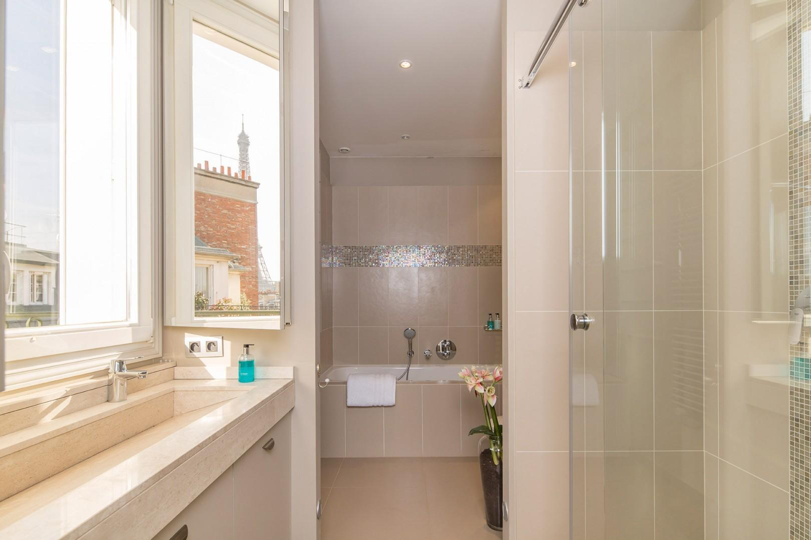 The luxurious en suite bathroom is equipped with a bathtub, shower, sink & toilet.