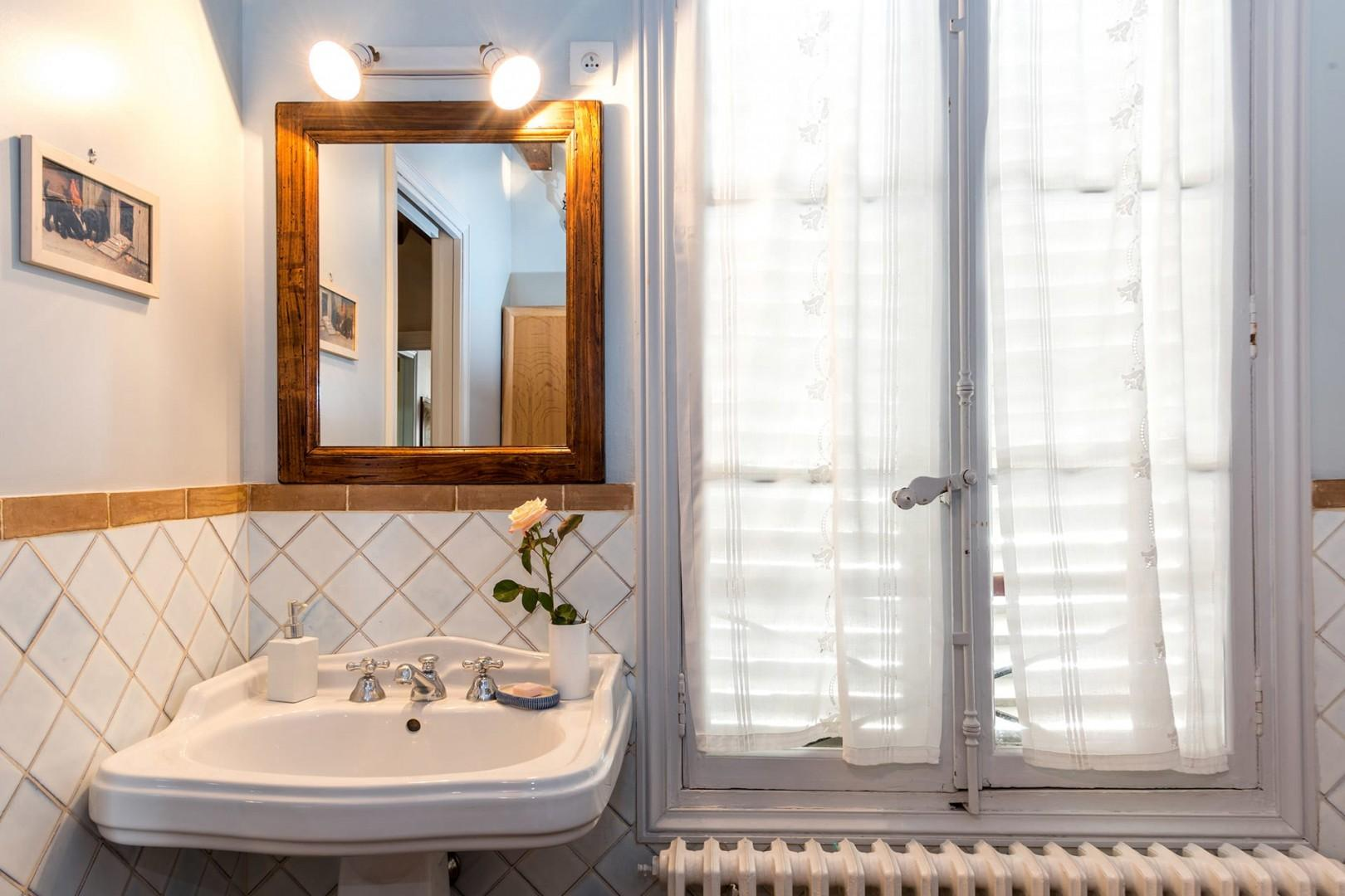 A large window fills the bathroom with great light.